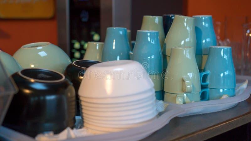 Hög av tvättade disk och koppar på magasin i buffét royaltyfri fotografi