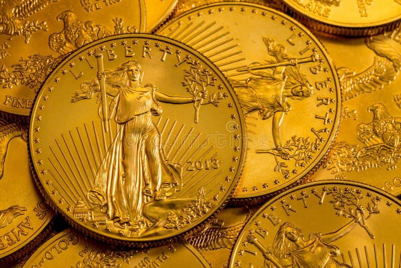 Hög av USA-kassan guld- Eagle ett uns mynt arkivfoto