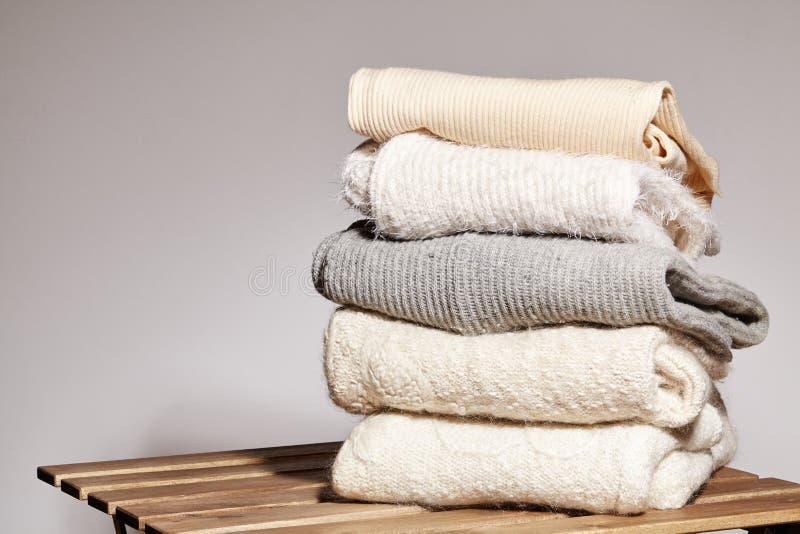 Hög av varma tröjor för mode på trätabellen Höst- och vinterullkläder Stuckit tröja eller omslag Anbudfärger arkivbild
