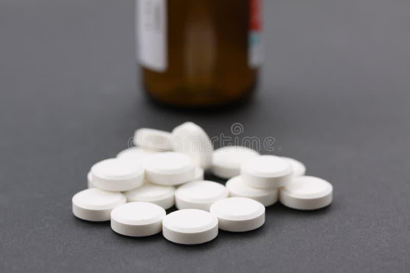 Hög av vita preventivpillerar med den bruna preventivpillerflaskan i backgroundllflaskan som illustrerar vitaminer eller böjelse  royaltyfria bilder