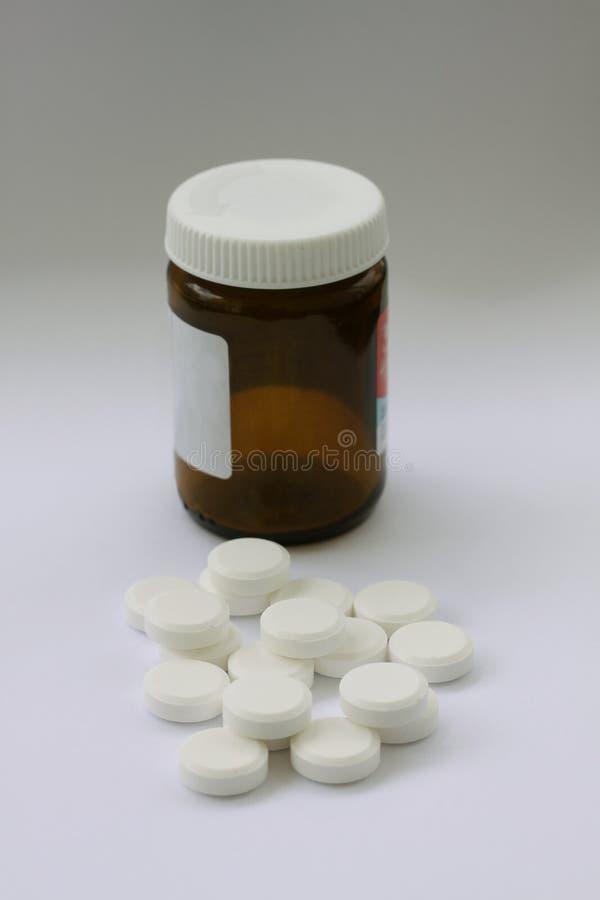 Hög av vita preventivpillerar med den bruna preventivpillerflaskan i backgroundllflaskan som illustrerar vitaminer eller böjelse  arkivfoto