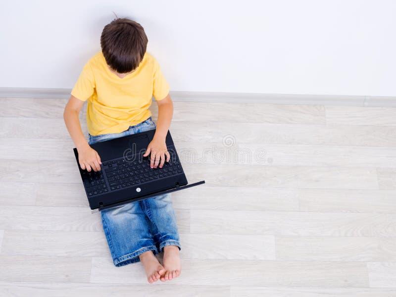 hög bärbar dator för vinkelpojke little som använder royaltyfria bilder