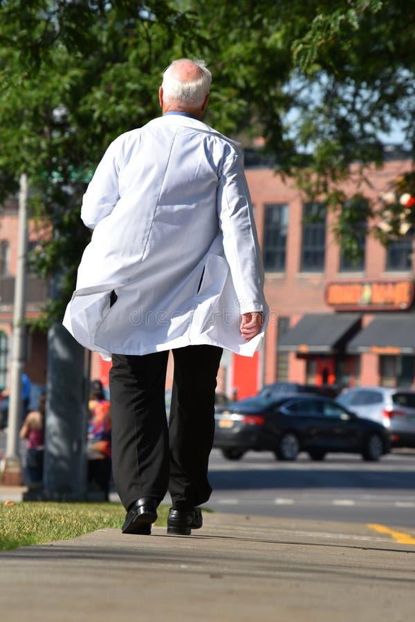 Hög bli skallig manlig doktor Walking On Sidewalk arkivfoton