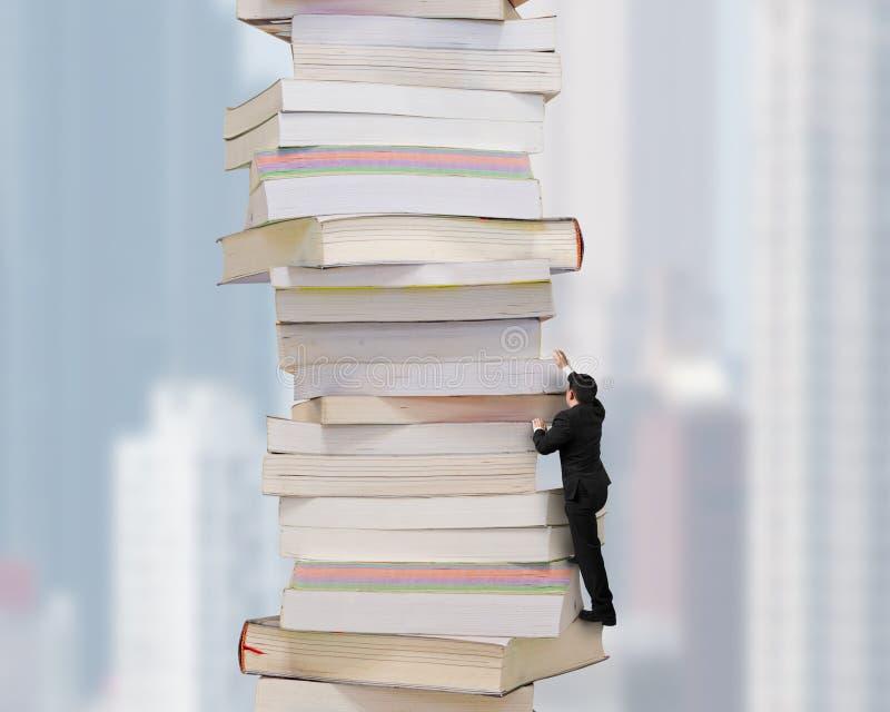Hög bunt av böcker med affärsmannen som klättrar den royaltyfri foto