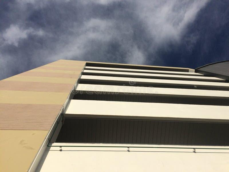 Hög byggnad med blå himmel och molnet arkivfoton