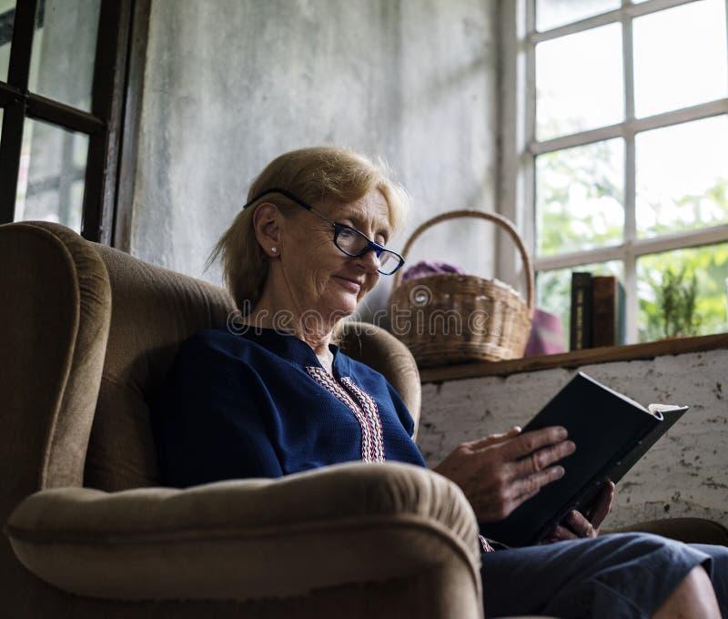 Hög caucasian kvinnasammanträdeläsebok på soffan fotografering för bildbyråer