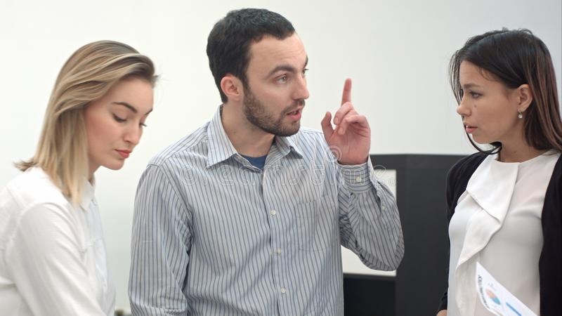 Hög chef som förklarar uppgifter till hans lag arkivfoton