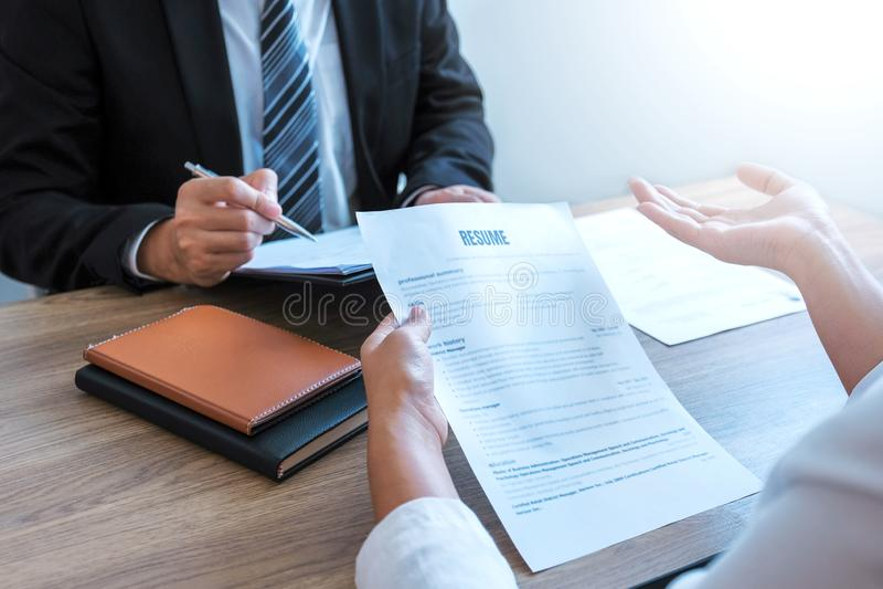 Hög chef som läser en meritförteckning under ett sökande och en rekrytering för möte för ung man för anställd för jobbintervju arkivbilder