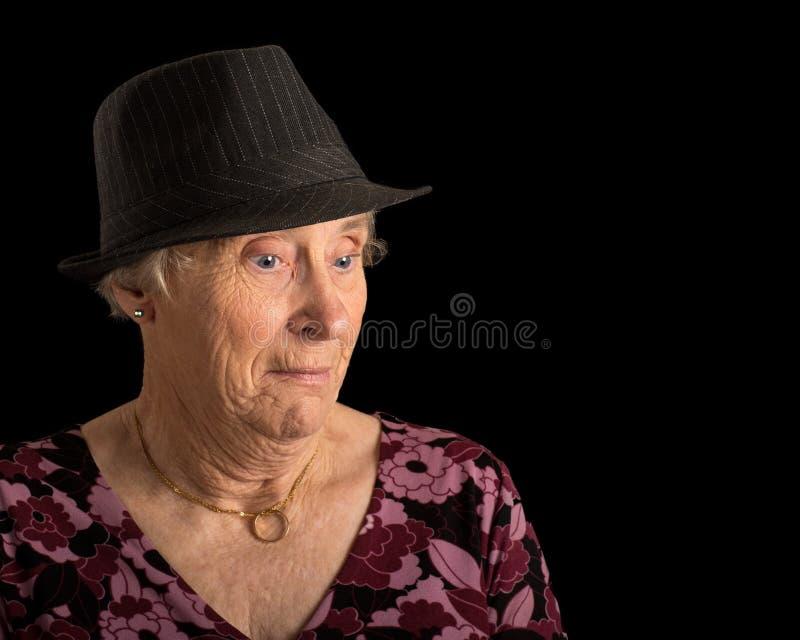 Hög dam med en chockad blick på hennes framsida som bär en fedora arkivfoton