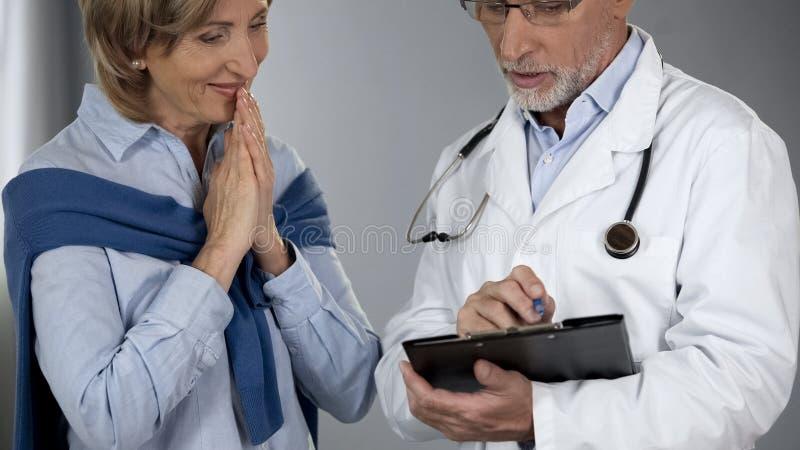 Hög dam som är lycklig att höra behandlingresultat, doktor som berättar goda nyheter, framsteg arkivfoto