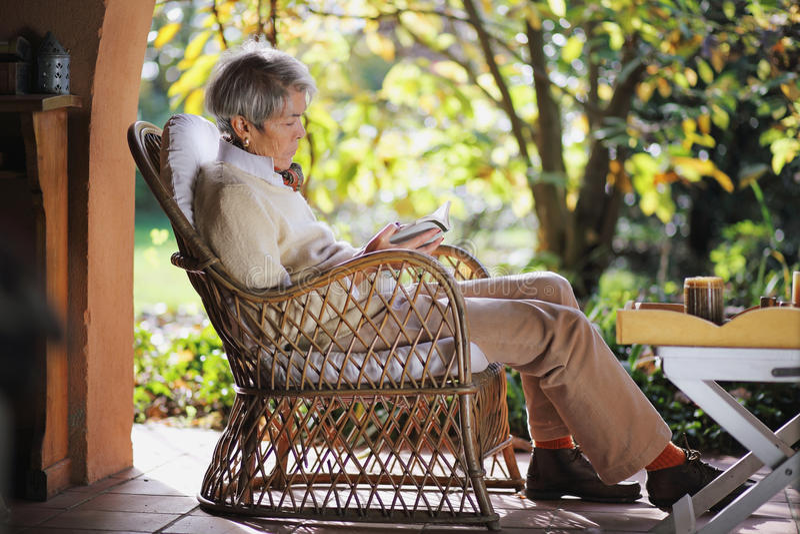 Hög dam som läser en utomhus- bok arkivbild