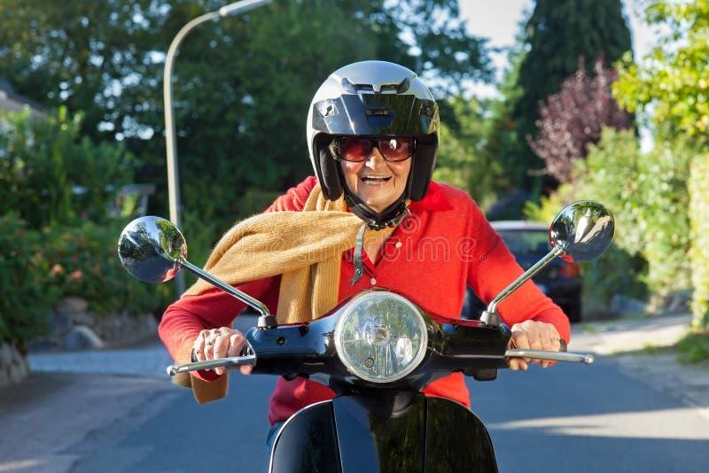 Hög dam som rider hennes sparkcykel fotografering för bildbyråer