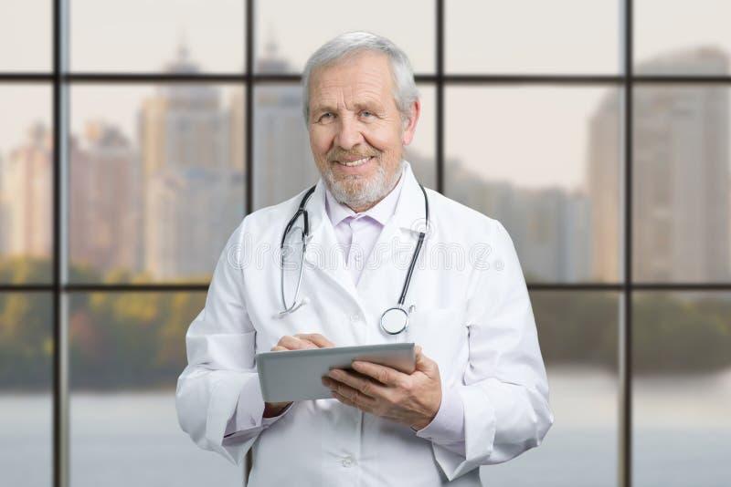 Hög doktor som använder hans minnestavladator på arbete royaltyfri bild