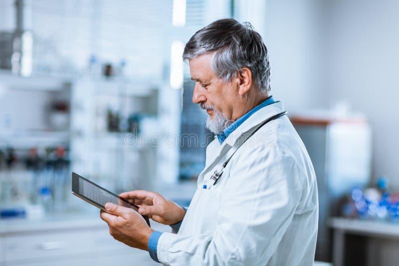 Hög doktor som använder hans minnestavladator på arbete arkivfoto