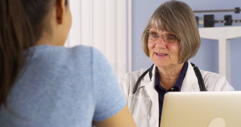 Hög doktor som konsulterar den latinamerikanska kvinnapatienten royaltyfri bild