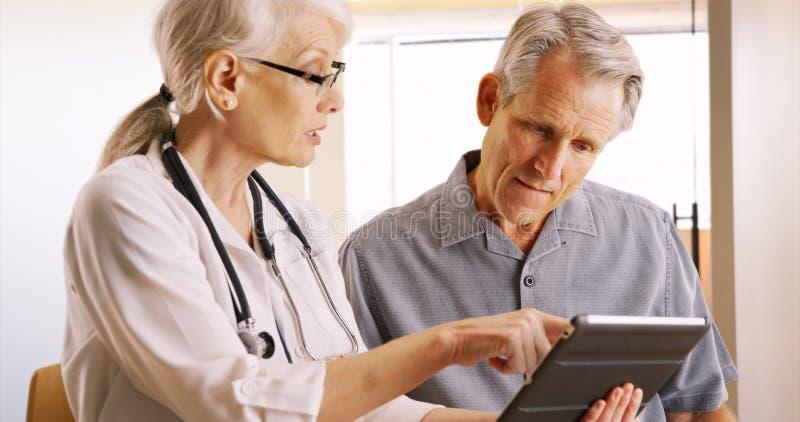 Hög doktor som uttrycker hälsobekymmer med den äldre manpatienten royaltyfri fotografi