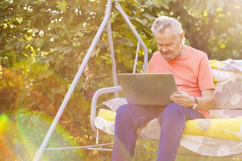 Hög elderyman som arbetar på ett bärbar datorsammanträde i sommarträdgård royaltyfria bilder