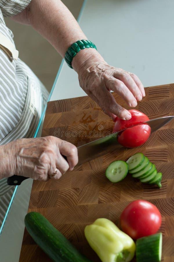 Hög eller äldre kvinna som lagar mat sallad i kök sund begreppsmat Sund livsstil Mormodern förbereder ett sunt mål för henne royaltyfri bild