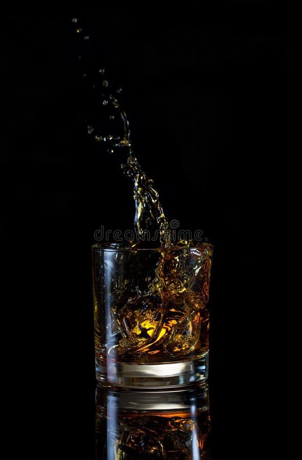 Hög färgstänk i exponeringsglas av whisky arkivbild