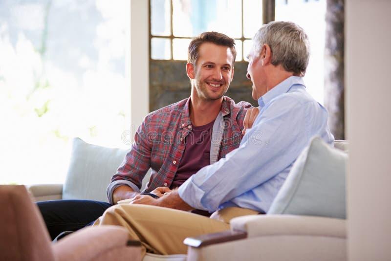 Hög fader With Adult Son som kopplar av på Sofa At Home royaltyfri foto