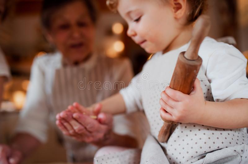Hög farmor med det lilla litet barnbarnbarnet som hemma gör kakor royaltyfria foton