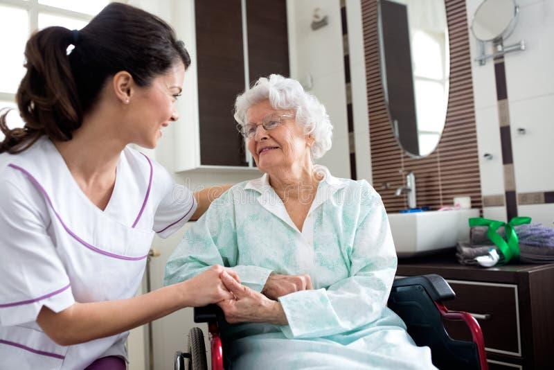 Hög gammal kvinna med sjuksköterskan arkivbilder