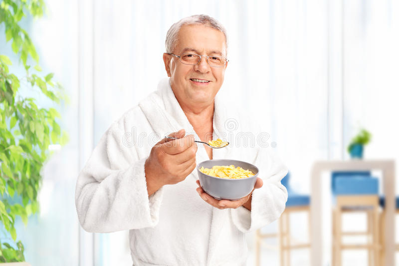 Hög gentleman som äter sädes- hemmastatt arkivfoton