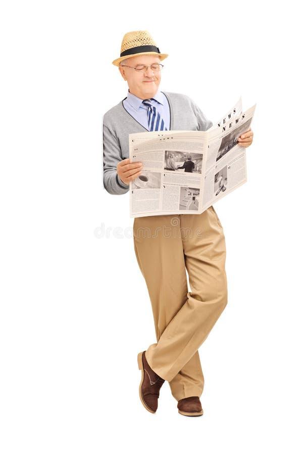 Hög gentleman som läser en tidning och en benägenhet mot en vägg arkivfoto