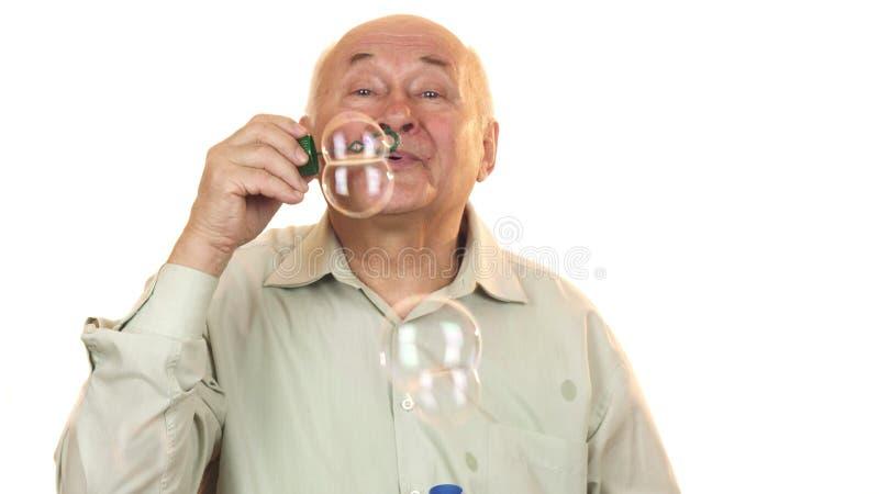 Hög gladlynt man som blåser bubblor som isoleras på vit royaltyfri foto