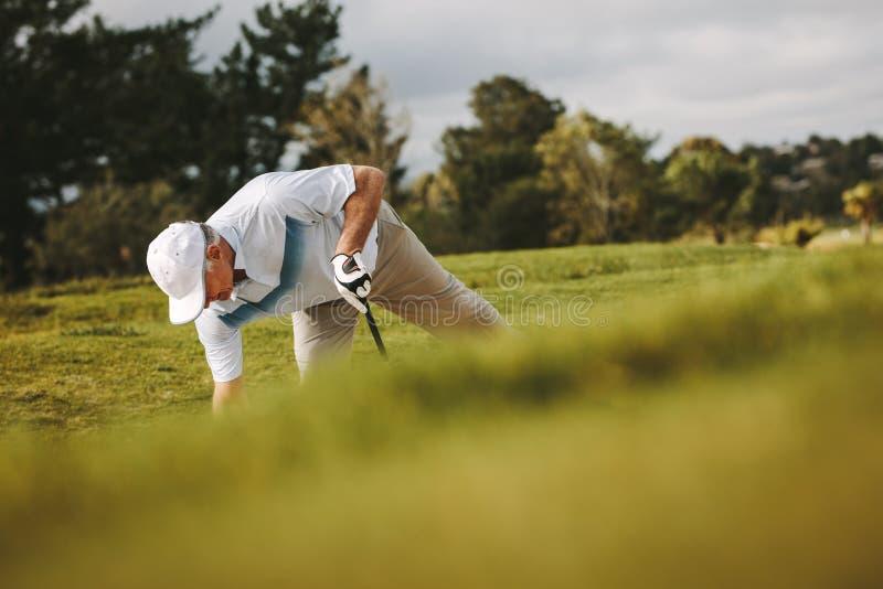 Hög golfare som spelar på golfbanan arkivbild
