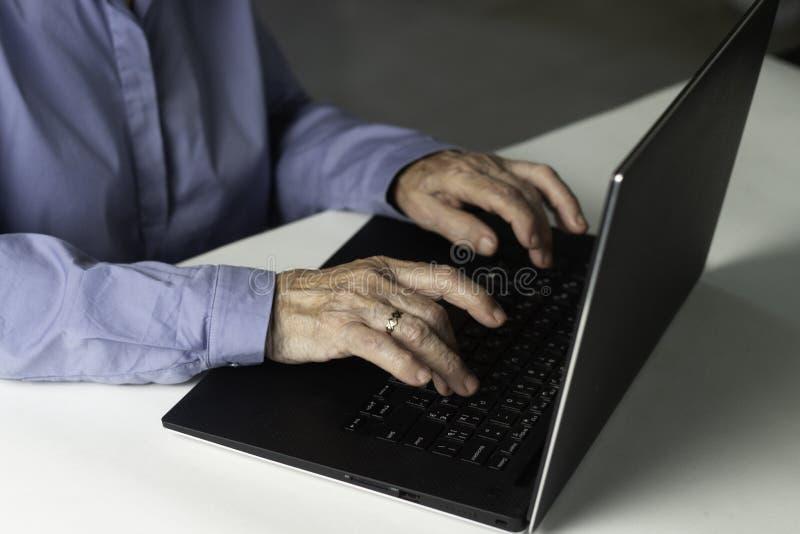 Hög gråhårig kvinna med bärbara datorn Äldre kvinnahandstilkorta avhandlingar på bärbara datorn som söker för information på inte arkivfoton