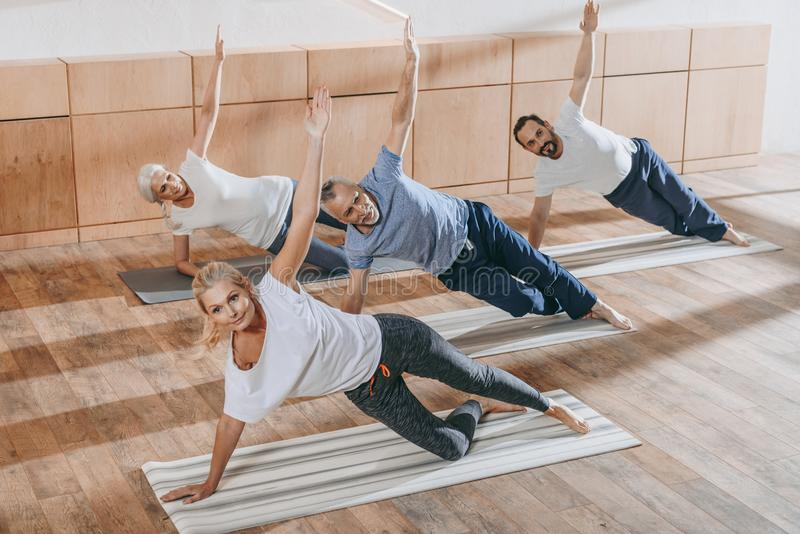 hög grupp människor med instruktören som övar på yogamats arkivbild
