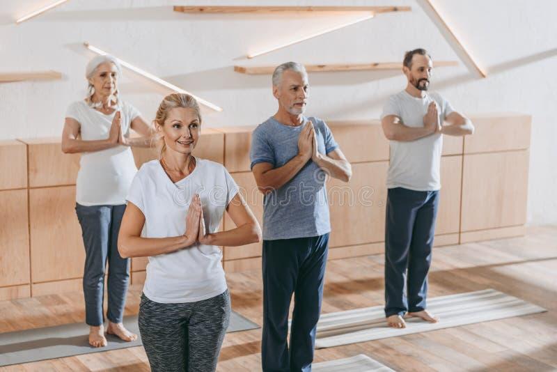 hög grupp människor med praktiserande yoga för instruktör royaltyfria bilder