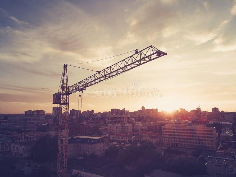 Hög gul kran som bygger ett hus i den härliga blåa himlen med moln Arbetare i byggnaden under konstruktion bygger a arkivbilder