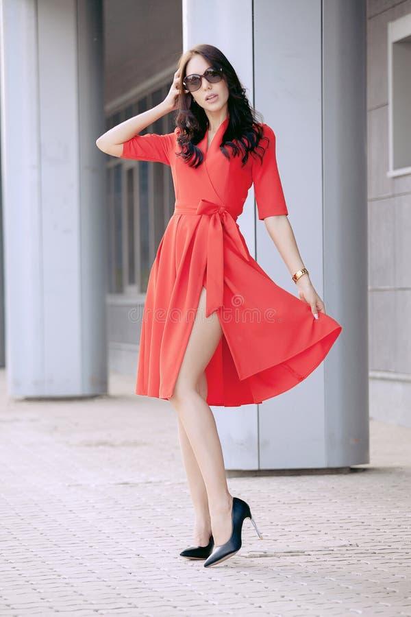 Hög-heeled den unga kvinnan för den härliga brunetten i en röd klänning, i svart skor, solglasögon som promenerar gatan Mode royaltyfri bild