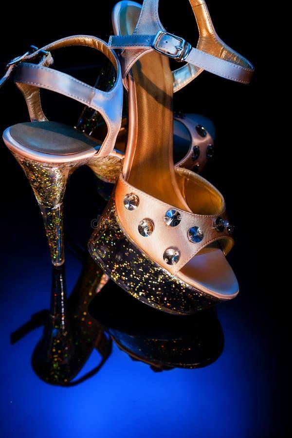 Hög-heeled skor för dans- och stripteasenummerställning på en reflekterande yttersida för exponeringsglas Champagne-färgade skor  royaltyfria foton