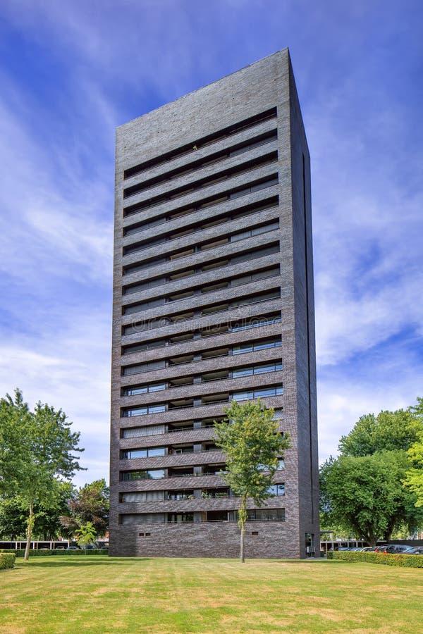 Hög hyreshus Cenakel, Tilburg, Nederländerna för löneförhöjningsvarttegelsten arkivbild