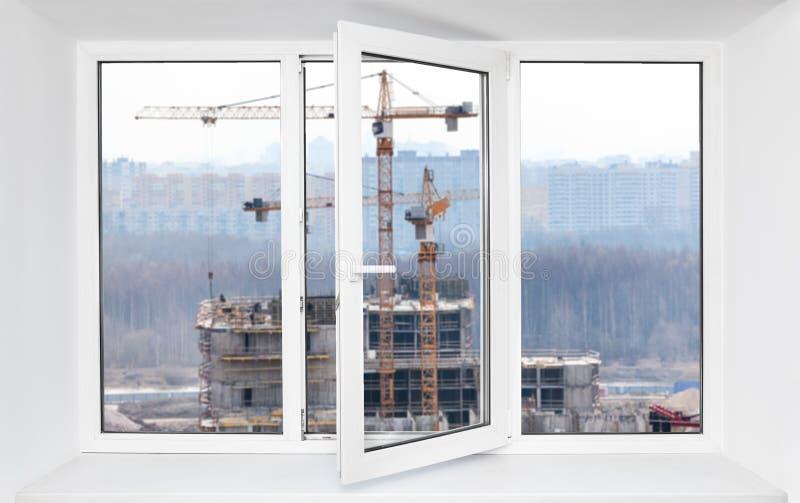 Hög immission för oväsen för konstruktionsplats, i öppnat en ram av pvc-fönster, sikt igenom fotografering för bildbyråer