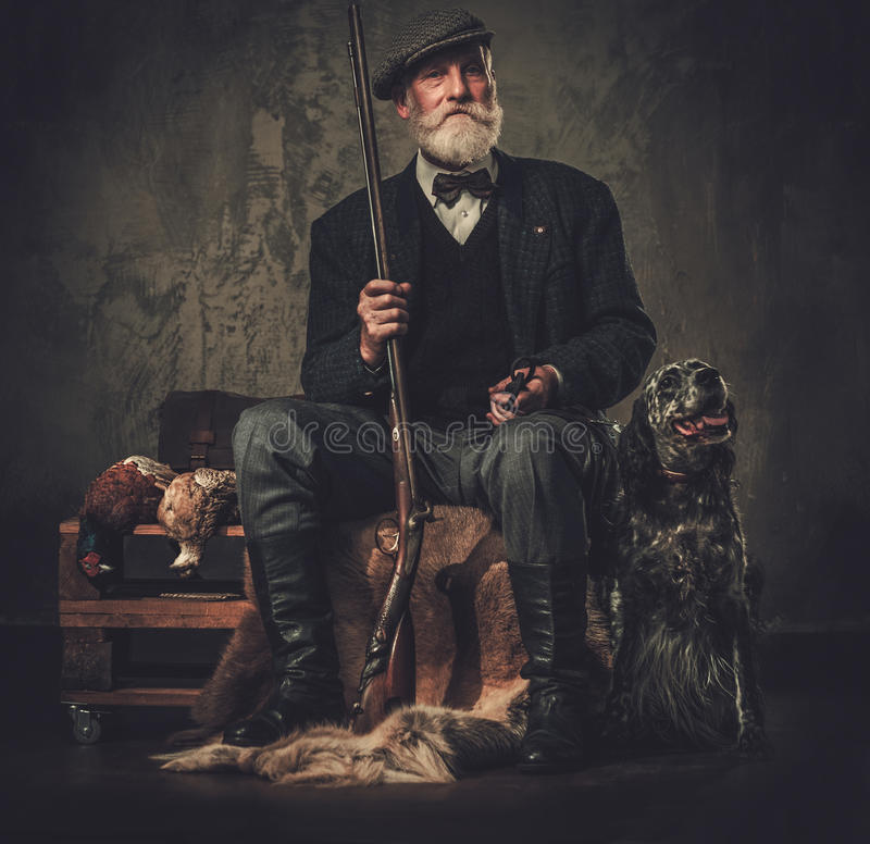 Hög jägare med en engelsk setter och en hagelgevär i traditionella skyttekläder, sammanträde på en mörk bakgrund royaltyfria foton