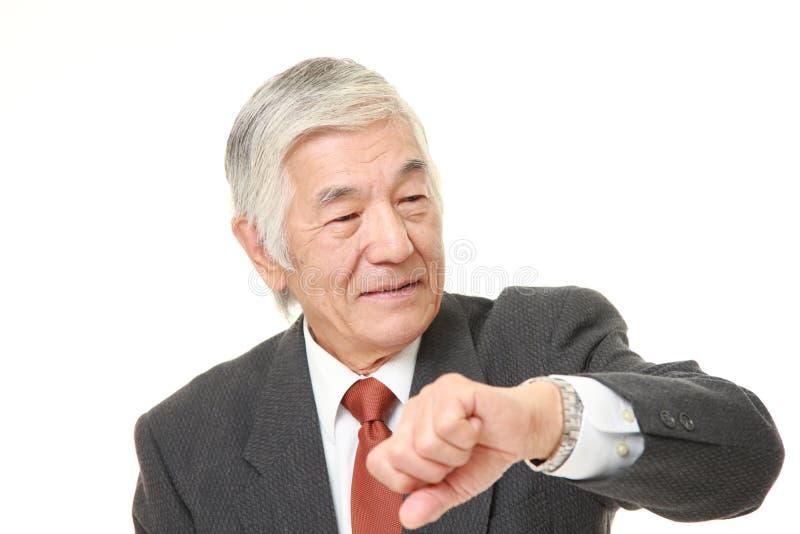 Hög japansk affärsman som kontrollerar tid på hans klocka arkivbild
