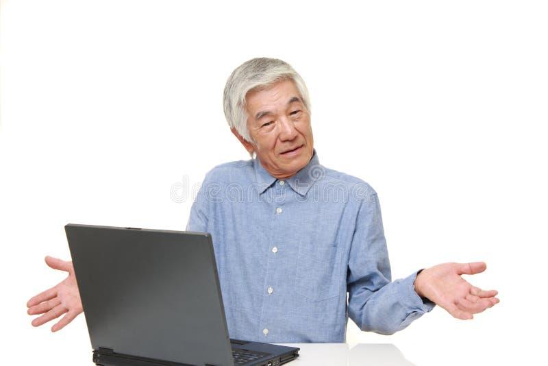 Hög japansk man som använder datoren som ser förvirrad arkivbilder