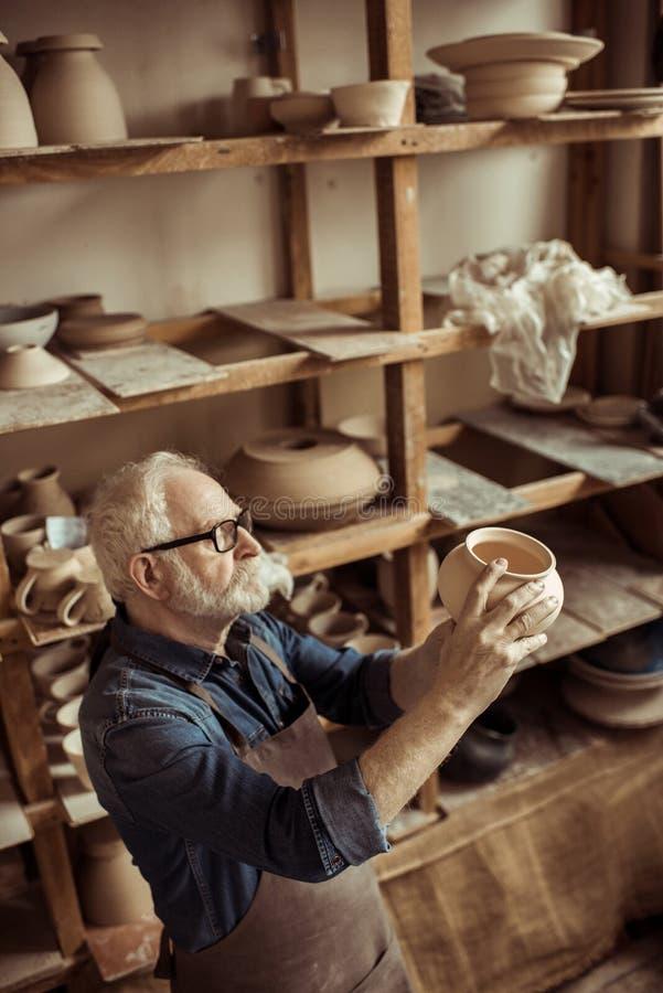 Hög keramiker i förkläde och glasögon som undersöker den keramiska bunken arkivbild