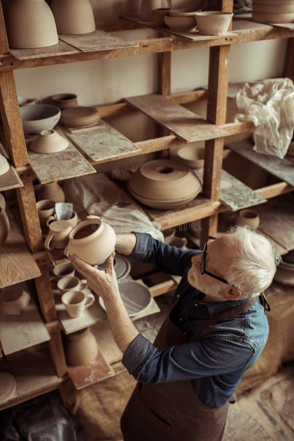 Hög keramiker i förkläde och glasögon som undersöker den keramiska bunken royaltyfria bilder