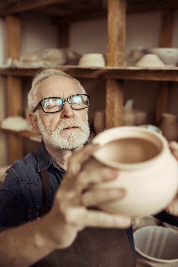 Hög keramiker i förkläde och glasögon som undersöker den keramiska bunken fotografering för bildbyråer