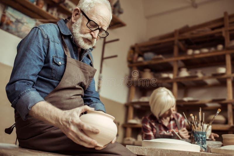 Hög keramiker i förkläde och glasögon som undersöker den keramiska bunken med kvinnaarbete arkivbild
