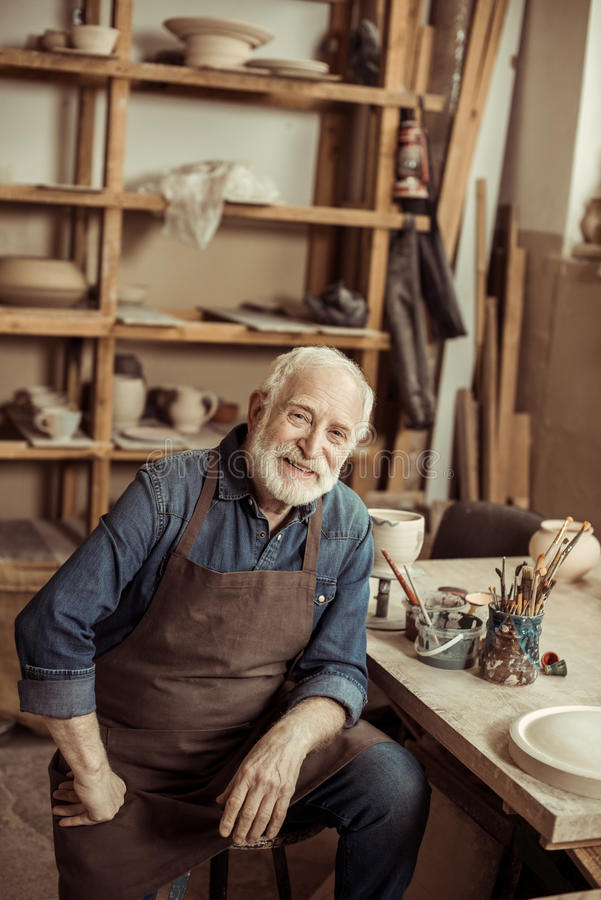 Hög keramiker, i ron sammanträde på tabellen och att se kameran royaltyfria foton
