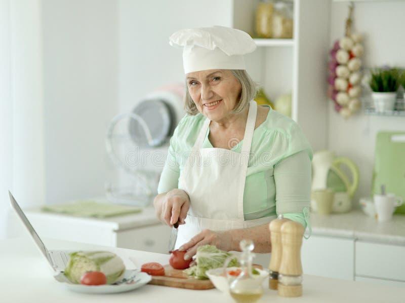 Hög kockkvinnastående på kök royaltyfri foto