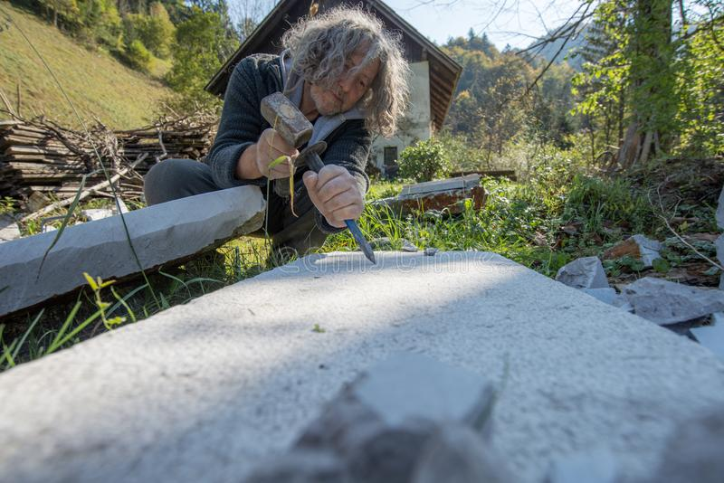 Hög konstnär som arbetar snida stenen arkivbild