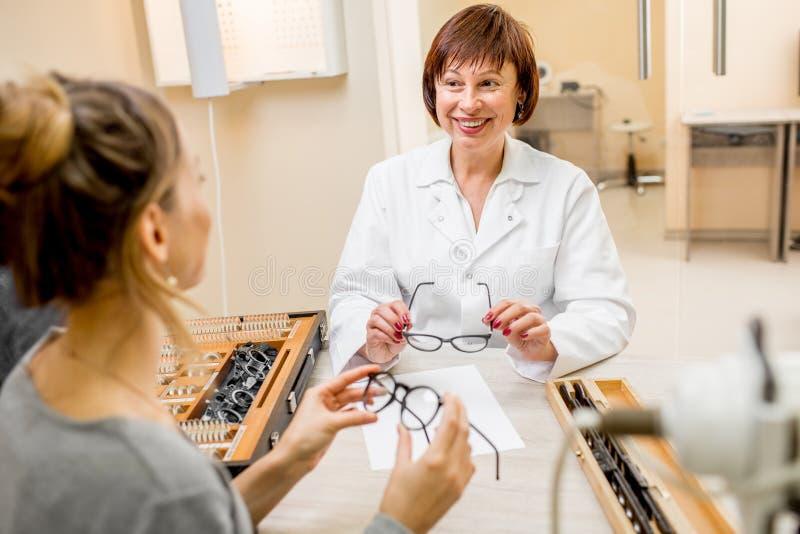 Hög kvinnaögonläkare med patienten i kontoret royaltyfri fotografi