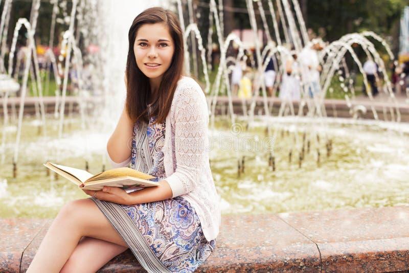 Hög kvinna för härlig brunett som studerar för hennes examina som sitter n arkivfoton
